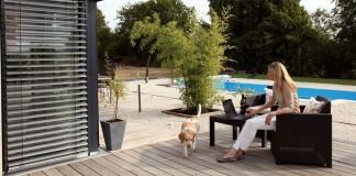 Terrasse des Fertighauses mit Frau Hartmann und ihrem Hund