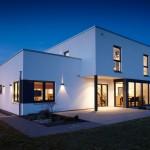 Fertighaus Bauhaus Außenansicht Rückseite mit Glaserker bei Nacht