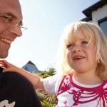 Papa und Tochter vor ihrem Einfamilienhaus