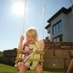 Tochter im Garten am schaukeln vor dem Neubau der Familie Leuthold