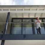Herr Lücke steht auf dem Umlaufendes Balkon des Bauhauses