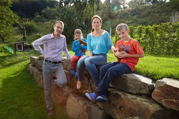 Familienbild mit Haustieren in idyllischer Umgebung. Die Hühner bewohnen das Häuschen im Hintergrund.