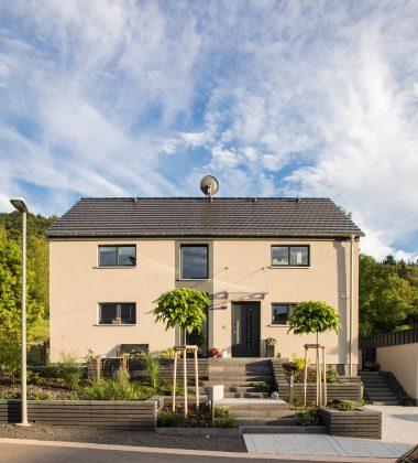 Ton in Ton: Die Betonsteine im Vorgarten vom Familienhaus haben die gleiche Farbe wie die Haustür, die Fensterrahmen sowie der schmale Fassadenstreifen. (Foto: FingerHaus)