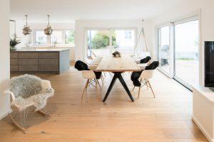 Edles Ambiente: Der 2,40 Meter lange Esstisch ist eine Sonderanfertigung und passt hervorragend zu den Bodendielen aus gekalktem Eichenholz. (Foto: FingerHaus)