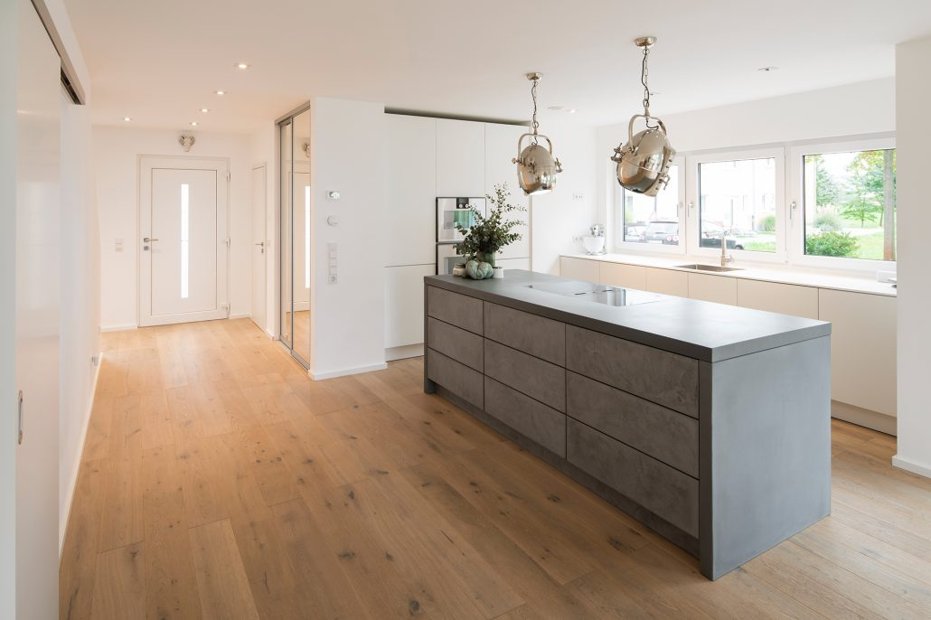 Großzügig: Der Eingangsbereich geht nahtlos in die Küche über. Die Kochinsel aus Beton entwarf ein Innenarchitekt. (Foto: FingerHaus)