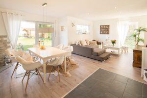Der Grundriss ist offen, aber strukturiert in verschiedene Wohnbereiche. Die optische Abgrenzung zur Küche schaffen die unterschiedlichen Bodenbeläge.