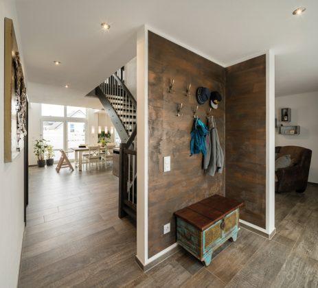 Bereits vom Eingangsbereich mit Geraderobe wird das offene Wohnen erlebbar, denn es gibt keine weiteren Wände und Türen zum Wohnbereich. (Foto: FingerHaus)