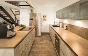Die Kombination aus Kochinsel links und Zeile rechts bietet Stauraum und Arbeitsfläche in Hülle und Fülle. (Foto: FingerHaus)