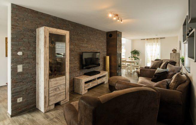 Heimkino und Loungebereich mit Polstersesseln und -liegen. Im Winter wärmt der eingebaute Kamin den gesamten Wohnbereich. (Foto: FingerHaus)