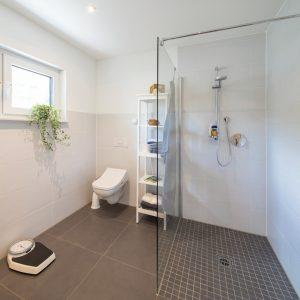 Barrierefrei: Die Dusche im Erdgeschoss ist bodengleich und nur durch eine einzelne Glaswand vom restlichen Bad abgetrennt. (Foto: FingerHaus)