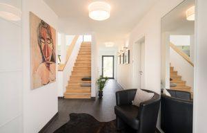 Willkommen: Ins Dachgeschoss führt eine Treppe aus Buchenholz. Hier unten ist der Boden mit großformatigen Fliesen ausgelegt. (Foto: FingerHaus)