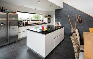 Profiküche: Zwei Induktionsfelder und eine Bratfläche machen das Kochen zum Vergnügen. Auch das Fenster über der Spüle erfreut die Bauherren jeden Tag. (Foto: FingerHaus)