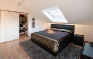 Schlafzimmer: Eine Schiebetür trennt den Raum von der Ankleide ab. Im Dachgeschoss sind die Räume, bis auf den Flur, mit Laminat ausgelegt. (Foto: FingerHaus)
