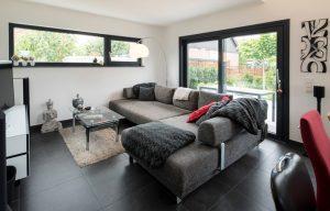 Ruhezone: Abends lässt es sich auf der Couch wunderbar entspannen. Verschiedene Grautöne mit roten Akzenten – dieses Farbkonzept gilt fast überall. (Foto: FingerHaus)