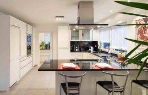 Der Küchentresen ist Treffpunkt des Hauses. Hinter der Küche liegt eine Speisekammer mit Schiebetür. (Foto: FingerHaus)