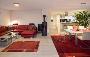 Rote Polstermöbel und Teppiche setzen Farbakzente in dem großen, hellen Raum. (Foto: FingerHaus)