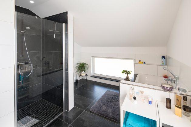 Badezimmer: Eine Fensterfolie schützt vor neugierigen Einblicken. Die dunklen Bodenfliesen ähneln denen eine Etage tiefer. Als Mosaik liegen sie in der Dusche. (Foto: FingerHaus)