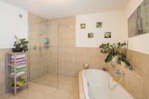 Walk-in-Dusche und schräg eingebaute Wanne: Das Familienbad lässt keine Wünsche offen. Die schicken Fliesen stammen aus der FingerHaus-Kollektion. (Foto: FingerHaus)