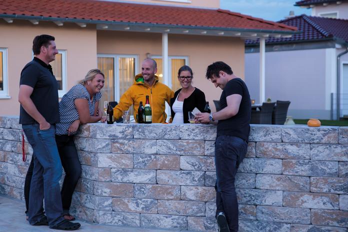 Die netten Nachbarn sind das Tüpfelchen auf dem i. Bei gutem Wetter wird die Grundstücksmauer zur Bar und der Hausherr schenkt spontan ein Glas Bier oder Sekt aus. (Foto: FingerHaus)