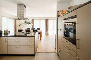 Von der offenen Küche sind es nur ein paar Schritte zum großen Esstisch. Die Küchenzeile mit dem Backofen wurde passgenau in eine Nische gesetzt. (Foto: FingerHaus)