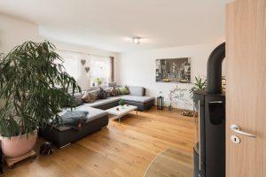 Das XXL-Sofa passt perfekt in den großen Wohnbereich. Von dort hat die Baufamilie den Kaminofen prima im Blick. (Foto: FingerHaus)