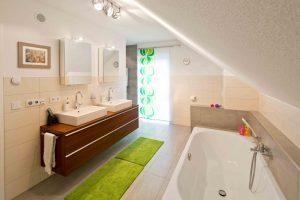 Traumbad im Dachgeschoss: Wohlfühlbereich mit Doppelwaschtisch, XXL-Wanne und bodengleicher Dusche. (Foto: FingerHaus)
