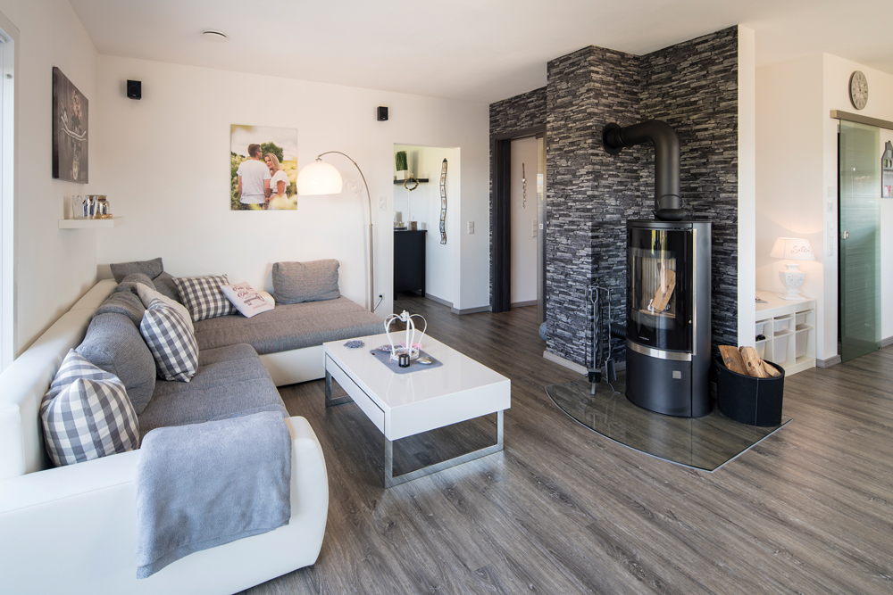 Im Wohnzimmer ist die Sofaecke gegenüber dem gemütlichen Kaminofen der Lieblingsplatz. Im Hintergrund zu sehen ist der Durchgang zum Arbeitszimmer. (Foto: FingerHaus)