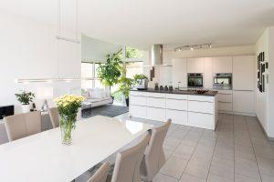 Küche mit Wintergarten: Auf dem weißen Sofa chillt am liebsten der Hausherr. Bei Bedarf wandelt sich die Ruhe-Ecke in eine Partyzone. (Foto: FingerHaus)