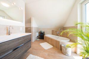 Elternbad: Die natürlichen Farbtöne der Fliesen holen mediterranes Lebensgefühl ins Haus. WC und Dusche liegen um die Ecke. (Foto: FingerHaus)