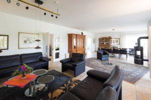 Wohnraum: Platz gibt es hier genug. Der warme Farbton der Fliesen harmoniert wunderbar mit den schwarzen Sitzmöbeln und den Schränken. Ein Kaminofen spendet Wärme und Gemütlichkeit. (Foto: FingerHaus)