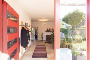 Willkommen: Vom Eingang geht der Blick fast ungehindert bis in den hinteren Garten. Die rote Haustür war ein Herzenswunsch von Christine Kraft. (Foto: FingerHaus)