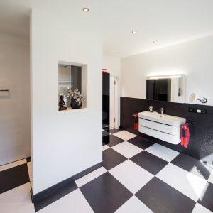 Schachbrett: Das klassisch schwarz-weiße Design des Badezimmers haben die Hausbesitzer 1:1 von der FingerHaus-Ausstellung übernommen. Die begehbare Dusche und die breiten Türen sind Teil des barrierefreien Wohnkonzepts. (Foto: FingerHaus)
