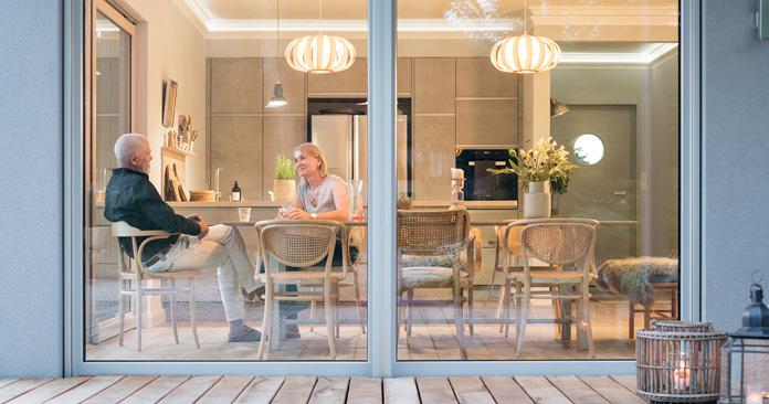 Wohnküche – Am gemütlichen Esstisch sitzen und durch die großen Fenster in den Garten schauen, das lieben die Lehmanns. (Foto: FingerHaus)